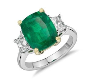 Cushion-Cut Emerald and Diamond Three-Stone Ring in Platinum and 18k Yellow Gold (4.90 ct center) (12x9.5mm)     One-of-a-kind elegance, this gemstone and diamond ring features a vibrant cushion-cut emerald complemented by brilliant trapezoid diamond side stones set in a classic platinum and 18k yellow gold design.
