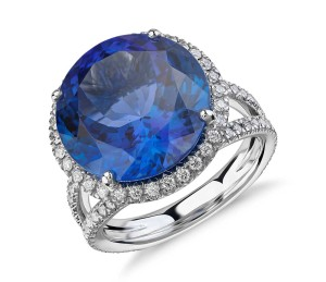Tanzanite and Diamond Halo Split Shank Ring in 18k White Gold (10.88ct center) (14.2mm)     Perfectly stunning, this gemstone and diamond ring features an impressive vivid tanzanite with a pavé diamond halo intricately set in 18k white gold.