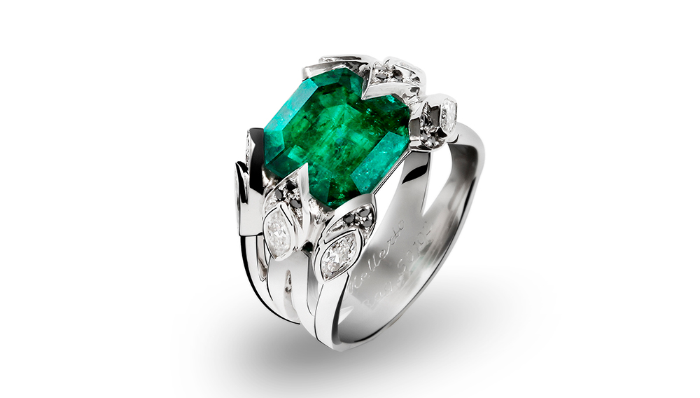 The centerpiece of the white gold ring is a brilliant green emerald with oval shaped diamonds and black accent diamonds