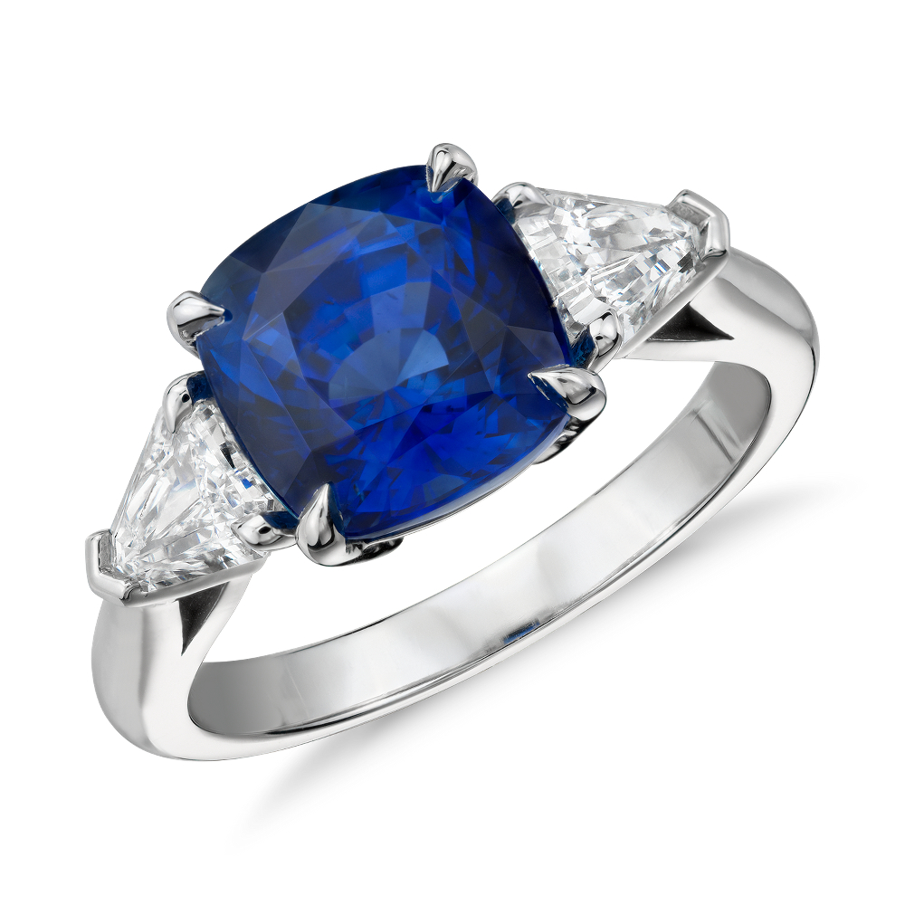 Cushion-Cut Sapphire and Diamond Three-Stone Ring in Platinum (4.27 ct center) Extraordinary elegance, this platinum ring showcases a vibrant 4.27 carat cushion-cut sapphire nestled between scintillating trillion diamond side stones.