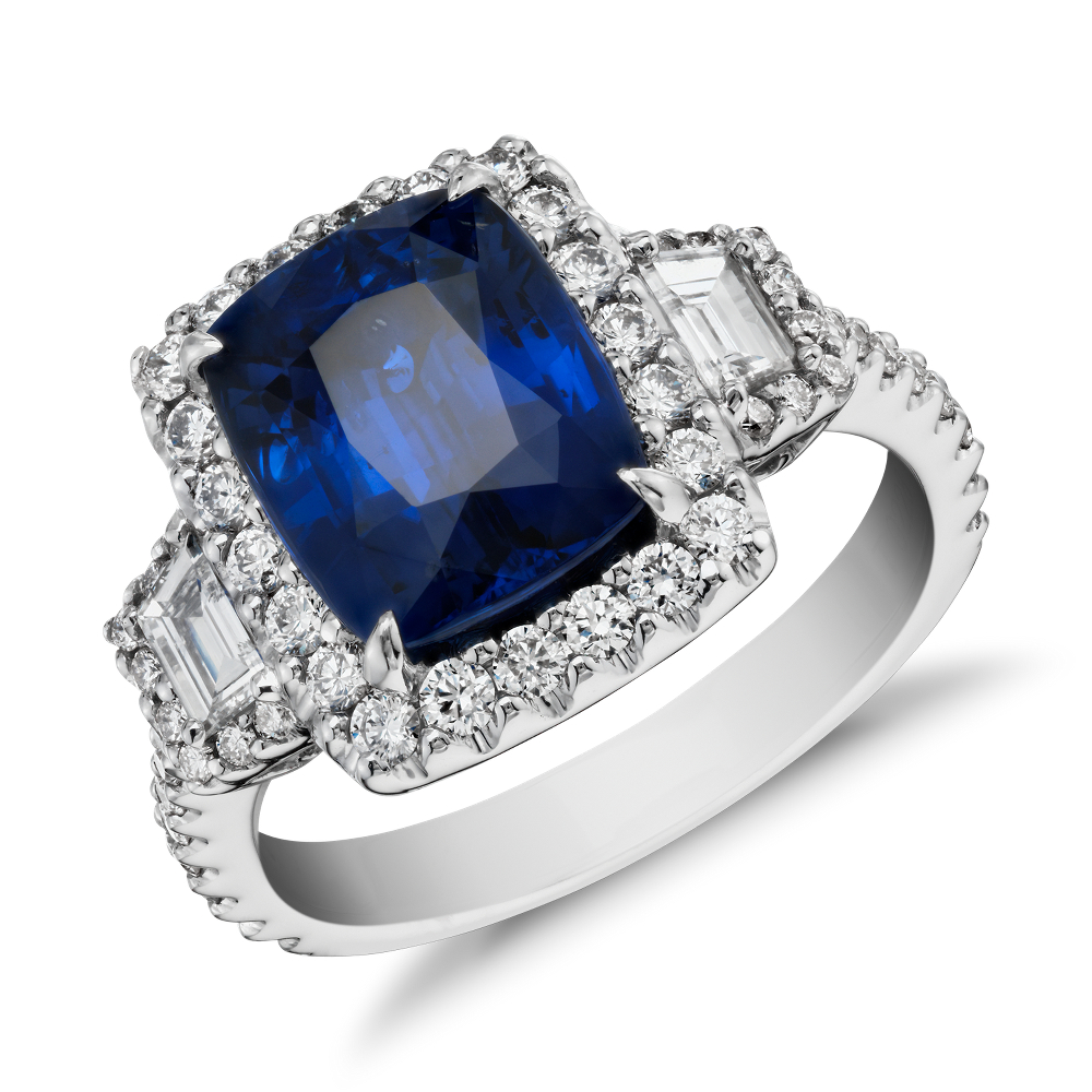 Sapphire and Diamond Halo Three-Stone Ring in 18k White Gold (3.65 ct) (9.8x7.8mm) Distinctly glamorous, this sapphire gemstone ring showcases a 3.65 ct cushion sapphire, step cut trapezoid side stones framed by a halo of brilliant pavé diamonds and a filigree flourish set in enduring 18k white gold.