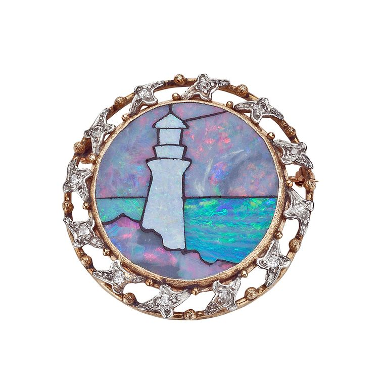 Leah Gordon Antiques inlaid opal brooch depicting a lighthouse on a rock outcrop overlooking the ocean. The brooch is highlighted with varying types of inlaid opal, surrounded by 12 old European and old mine-cut diamonds, set in 14ct gold.