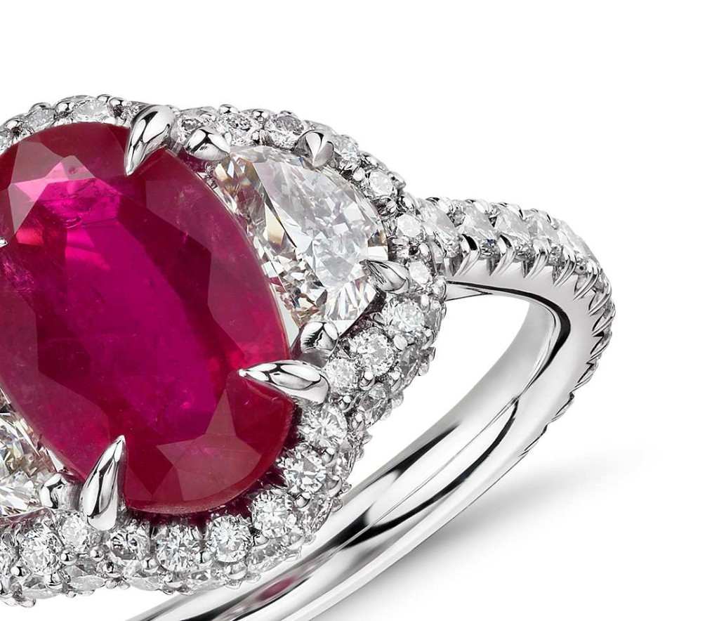 Uniquely stunning, this gemstone ring showcases a lively 2.24 carat oval ruby and two brilliant half-moon diamonds surrounded by halo of pavé-set round diamonds set in platinum with an 18k yellow gold accent. The exquisite ruby is a scarce, non-heated gemstone