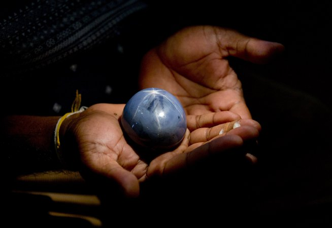 A Sri Lankan displays a star blue sapphire, claimed to be the worlds biggest star blue sapphire on his palm in Colombo, Sri Lanka, Friday, Jan. 8, 2016. Gemological institute of Colombo, a local gem industry body has certified that the gem weighs 1,404.49 carats(281 grams).