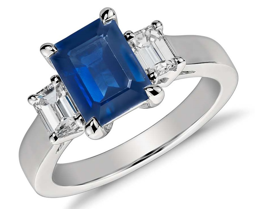 Emerald Cut Sapphire and Diamond Ring in Platinum (8x6mm) Elegantly refined, this gemstone and diamond ring showcases an emerald cut sapphire complemented by two matching emerald cut diamonds and set in enduring platinum.