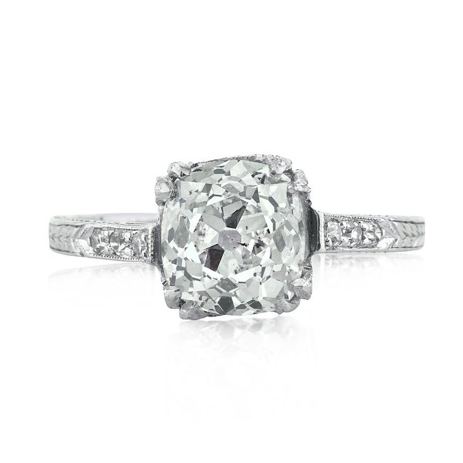 Enchant your sweetheart with vintage charm. This gorgeous old mine cut engagement ring is a sweet beauty with a lot of character. The antique style platinum setting has a few old round cut diamond accents and is covered in lovely hand engraving. Sitting pretty atop the setting is a glamorous 2.02ct old mine cut GIA graded at I-SI1. The cushion shaped stone faces up very white and brilliant. The facet pattern is true to old cut stones and is quite stunning. Seal your love by presenting her this one-of-a-kind antique style ring.