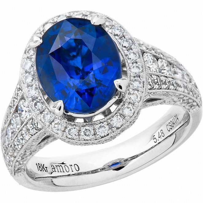 An oval cut genuine Ceylon Sapphire weighing approximately 5.48 carats, surrounded by two hundred and six round brilliant cut genuine Diamonds weighing approximately 1.84 carats, VS2-SI1 in clarity and G-H in colour set in an 18kt white gold AMORO heart prong setting. Engraved with AMORO and accented with a Diamond starburst.