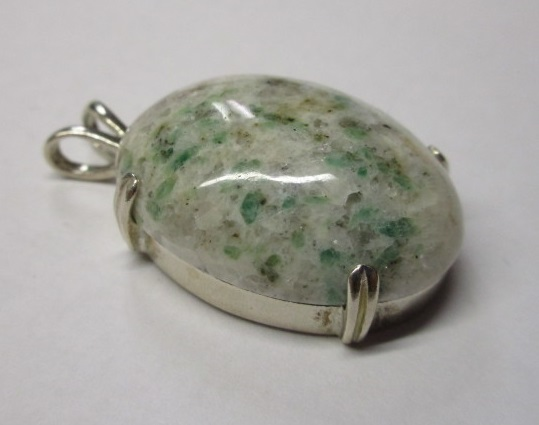 A beautiful custom-cut emerald in matrix mounted in a pendant.