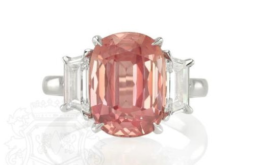 s feminine as can be! So light, a blush peachy pink, soft and warm, yet still refreshing; this 8.27ct pinkish orange untreated Padparadscha sapphire is truly magnificent not only as a precious rare gemstone, but also for its delicate beauty and aesthetic sensibility set in an elegant platinum and diamond three stone ring. This Padparadscha engagement ring is truly a one of a kind. Being a completely natural and unheated Padparadscha with an included report from the prestigious Gemological Institute of America, you can be sure you''re getting the real McCoy. Complementing the fineness of the center sapphire, the 1.03ctw of trapezoid diamond side stones are both E-color and VVS2. With a sapphire as rare as the Padparadscha, expect to wait some time before you see a stone as beautiful as this one.