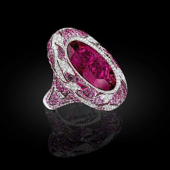 Sapphires and white diamonds leaves embrace the intense Rubellite stone.