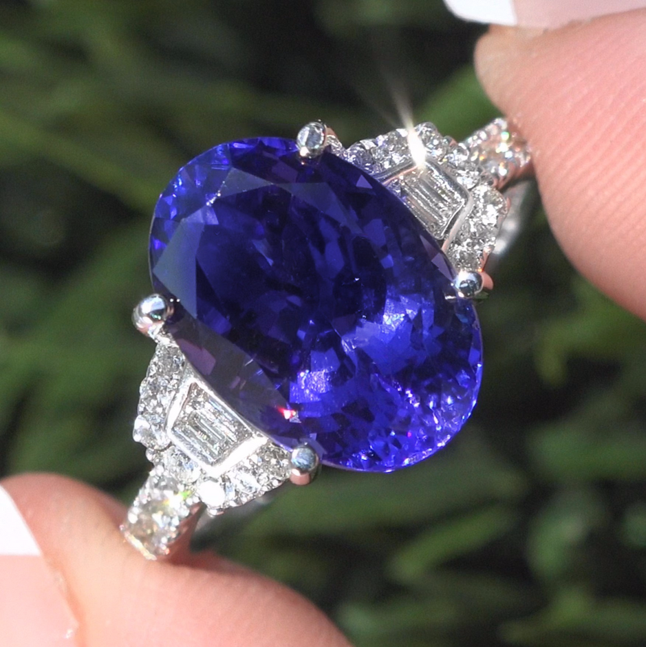 6.06 Total Carat Weight Natural Tanzanite & Diamond Ring. This stunning 5.60 carat (exact carat weight) Internally Flawless Clarity Tanzanite specimen features a stunning Violet-Blue color and is accented with a gorgeous array of natural round brilliant & baguette colorless & near colorless F-G color VS1-VS2 clarity diamonds totaling 0.46 carats. These diamonds light up this solid 18k white gold setting with sparkle and fire. The setting is a true fine jewelry masterpiece with an elegant custom design featuring 26 large accent diamonds. This extraordinary estate ring has it all and would be a great addition to any fine jewelry collection.