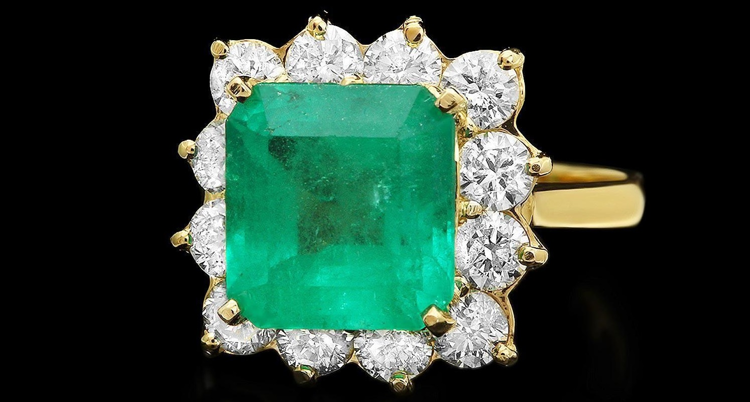 This elegant ladies ring is crafted in solid 14k Yellow Gold and features a 4.30 carat 100% Natural Emerald mined from Colombia + accented with 12 sparkling eye-clean natural Diamonds, totaling 1.80 carats.