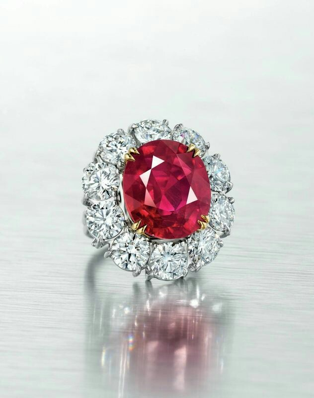 An exceptional 15.03 carat 'pigeon blood' Burmese ruby and diamond ring. Set with an oval-cut ruby, weighing approximately 15.03 carats, within a round brilliant-cut diamond surround, ring size 5 ¾, mounted in gold