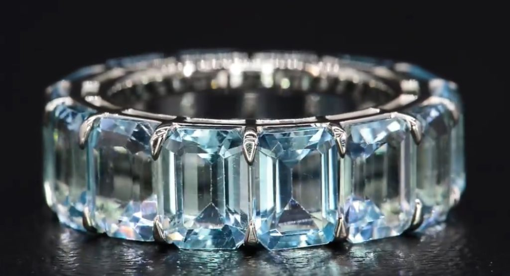 A gorgeous eternity band with natural, untreated, emerald-cut blue topaz gemstones.