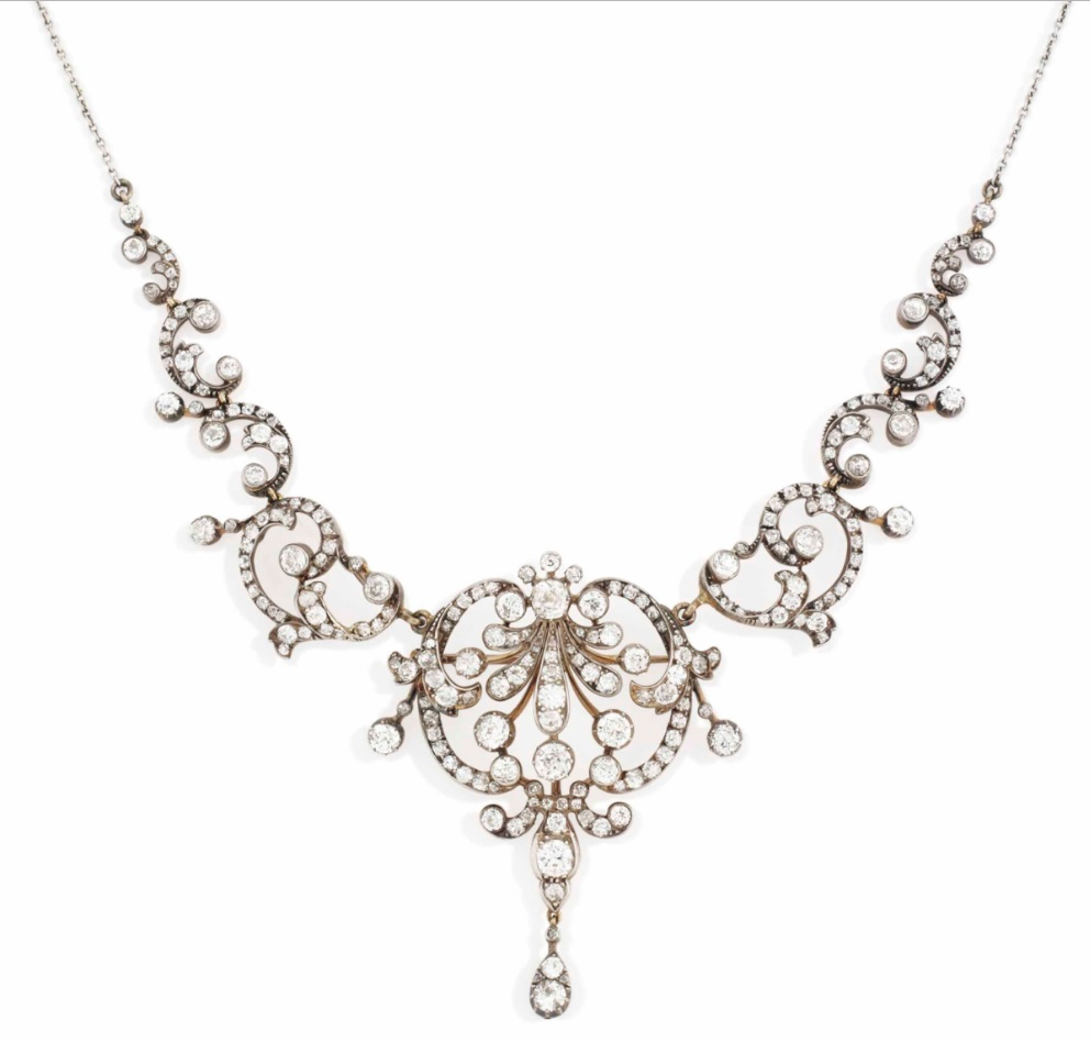 A late 19th-century diamond tiara / necklace. The graduated scrolling old-cut diamond-set panel, with central stylised shell motif and trefoil surmount, to a pear-shaped diamond-set finial, with associated fine-link chain necklace, mounted in silver and gold, central panel detaching to form a pendant / brooch, later adapted, tiara frame deficient, circa 1880, 40.2 cm. Sold for £8,125 on 2 December 2015 at Christie's in London